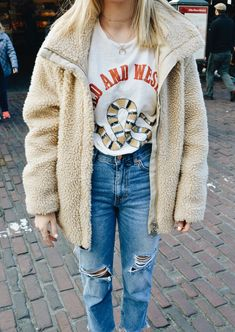 Mom jeans paired with a graphic tee and faux fur coat is a total 90's look