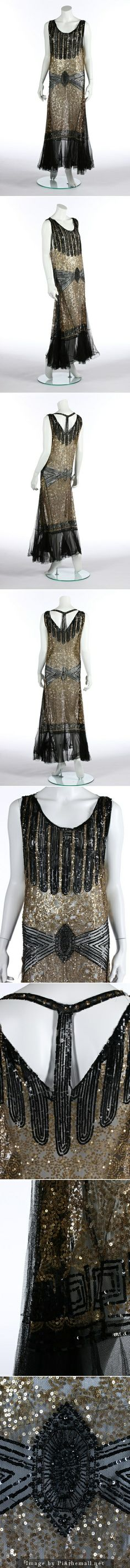 A black and gold sequined tulle evening gown, circa 1930. with bugle beaded 'girdle' and central medallions, gold curleque ground, vertical centre-strap to back, flounced hem. KTA