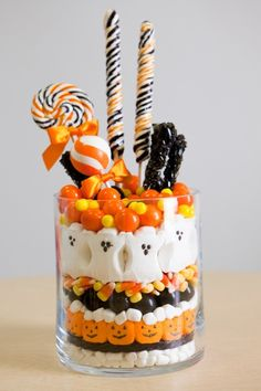 Halloween Centerpiece ~ layered mini marshmallows, black licorice, pumpkin Peeps, more mini marshmallows, large black gumballs, candy corns, ghost Peeps, large orange gumballs and mini yellow gumballs. She stuck a variety of lollipops into the top.