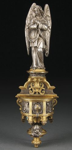 A VERY FINE FRENCH SILVERED AND GILT BRONZE ANGEL HOLY WATER FONT, 19TH CENTURY, VICTOR PAILLARD. The angel sculpted above an ornate font set with a winged cherub head. Stamped on verso VP beneath crown. Height 11 inches (28 cm).