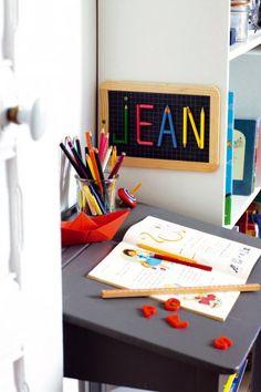 Ardoise d'écolier avec prénom Jean écrit en lettres de crayons de couleurs collés, comme un tableau