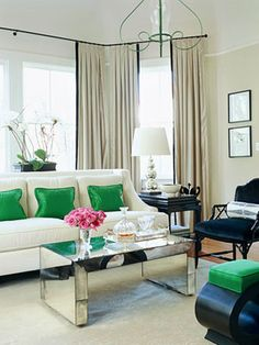 White modern furniture with pops of green is just lovely. Emerald green chic living room design. Love the Hollywood Regency mirrored coffee table and upholstered black faux bamboo chairs! Gray beige paint wall color. Green cream white black tan living room space!