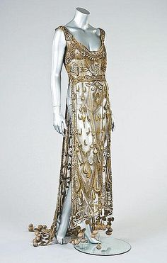 An embroidered gold tulle tabard, circa 1910-12, worked in raised silver and gold threads, blue floss silks in grand belle epoque style, the trained hem adorned with gold thread rouleaux and padded pom-poms