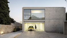 This monolithic concrete house in an affluent area of Porto presents a robust facade to the street, but opens up on its sidetowards its garden.