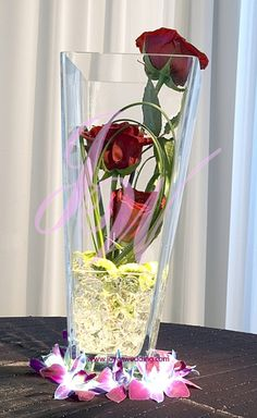 This #centerpiece of #three #red #roses #submerged in #square #V-shape #glass #vase with #jelly #beads and #purple #orchids #around is #modest and #elegant. #Nice for both #wedding and #corporate #floral #décor