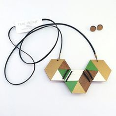 Geometric designed laser cut timber hand painted in gold, green and white. Bound and strung with high quality leather lace. If you haven't discovered this shop yet, you are truly missing out on some amazing one of a kind handmade jewelry with bold designs that are truly unique.  See more atwww.huisdesign.etsy.com