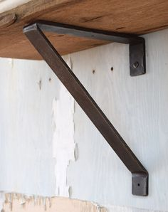Sold by rtidforged.com Shelf Bracket - Style 05 Aether $ 38 Hand-hammered metal shelf bracket with blackened iron finish. Heavy-duty industrial look and feel. This shelf bracket measures 11 inches heigh by 1 1/2 inches wide and 9 inches from the wall. We recommend a shelf bracket every 36 inches.  All our brackets are made to order. Please allow approximately 2 to 3 weeks for delivery.