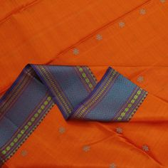 With its various vivid colors and lush details, this Sarangi silk sari is one bustlingly beautiful creation. The body comes in a rich, bright orange, subtly adorned with tiny dots...