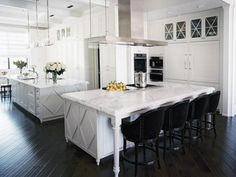 In this luxurious Hamptons-style kitchen, designer Jamie Herzlinger created an updated traditional look that's long on luxury. Acres of white marble top the dual islands, complementing the custom millwork's graphic interlocking diamonds, a motif repeated on the upper cabinets that line the long walls. Panels cover the built-in refrigerators, for a sleek, integrated look.