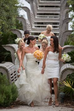 A bride in a @verawanggang wedding dress and her bridesmaids in @m_lhuillier bridesmaid dresses | Brides.com