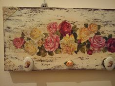 Decoupaged wood with drawer knobs attached.