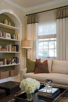 "by Annette English  Outside woven woods mount at the drapery height with the drapery featuring a 12"" fabric splice with braid trim... Lemon Verbena 7726 by Sherwin Williams is similar.... shade starting over window and lined up with curtains... like the bookshelf arrangement, the drapes, the olive background of bookcase; contrast.... add the bookcase with a painted backing to add colour to room"