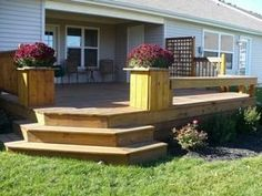 deck with a bench around the edge with planters in the corners!