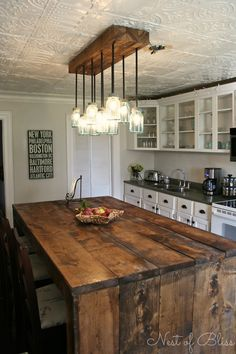 A great diy rustic wood island made with barnwood, mason jar lighting, and beautiful detail in the ceiling.