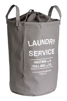 Laundry bag: Laundry bag in ecru cotton twill with a text print, two handles, a plastic coating on the inside and a top section in thinner fabric with a drawstring closure. Size 34x52 cm.
