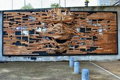Street Artist Transforms a Billboard into a Sculptural Relief Using Reclaimed Wood