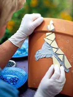 Start your design   Sketch your design on the pot, indicating where you want certain sections of color or specific patterns. Wearing gloves and using the plastic knife, spread a 1/4-inch layer of thin-set mortar over the first section of your design. (For larger projects, use a notched mortar trowel to spread the mortar.) Do one area at a time; the mortar will begin to harden in 15 minutes. Press mosaic pieces into the wet mortar, spacing them about 1/4 inch apart. Repeat with remaining…