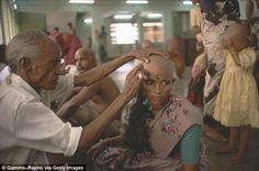 Women wait in line in at a temple in southern India where they have their heads shaved, pi...