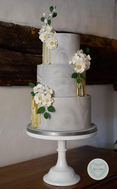 Marbling effect three-tierd grey wedding cake with sugarflowers and dripping gold