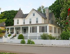 """Beautiful old Victorian home on Mackinac Island, also on the """"main drag"""". I love the combination of open porch and enclosed porch. This house faces south, so the enclosed porch would be cozy when sun is shining but the weather is cool. The curved section of porch would be quite difficult to build in the old days, adding to the cost of construction. Such curved features were often done as a subtle way of bragging about one's wealth."""