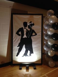 Black dancing couples silhouettes. Trace silhouettes on black paper and then glue on white. Decorate dancers with beads, feathers and glitter paper. Make a frame out of black wood and a black wooden stand to make it free standing. It is 7 feet tall and 4 feet wide. Put a spot light on the front and add balloon towers.