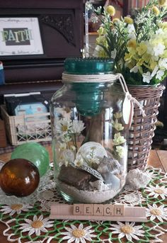 Beach in a Jar ~ By repurposing an old pickle jar (gallon size) and large blue glass insulator, I created a beach vignette using sand and found objects like seashells and driftwood, then placed in small silk daisy flowers and tied rope string around the top to finish it. Imagine a lit candle glowing in the inside of the blue insulator! Follow the link to Like my Facebook page, follow me on Instagram! Savvy Art