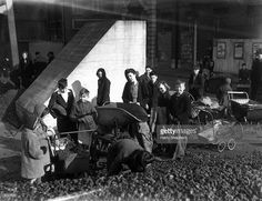 People queue up at a London depot for their wartime ration of coal and coke. Prams provide a handy receptacle for the monthly supply, 7th March 1944.