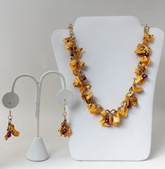 This lovely necklace and earring set features yellow-dyed shells and purple-dyed freshwater pearls. All wirework is handmade with exception of
