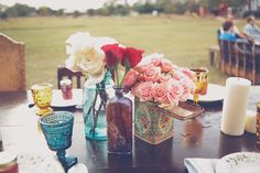 i love the mix of mason jars, amber bottles and vintage tins as centerpieces