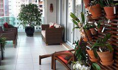 Painel em madeira, com vasos de barro e orquídeas.