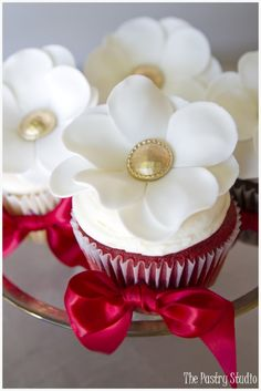 Christmas Cupcakes: Open blossom sugar-paste florals with gold centers & ruby red bows. By The Pastry Studio