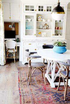 Kitchen with white table, bright blue flower vase, patterned rug, wood floors, wooden chairs, white cabinets with gold details, desk space with white and wood chair and bulletin board
