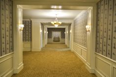 """Plaza Hall: Set of the Plaza hotel built on a stage in two versions.  Custom designed flocked wallpaper was the common element between the first """"crummy"""" suite and the second """"General Sherman"""" suite.  This long hallway was especially designed to acomodate the choreography of the characters as they walk towards each of the suites. As seen in Columbia Pictures' AMERICAN HUSTLE.  Production Design by Judy Becker Photo by:  Alex Linde"""