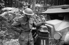 A soldier of 51st Highland Division shows off his captured German steel helmet fixed to the front of his truck, River Bresle area, 6 - 8 June 1940.