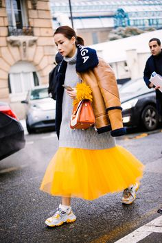 The Best of Paris Street Style FW18 over sized sweater with a bright egg yolk colored pooffy tulle skirt. and dad sneakers.