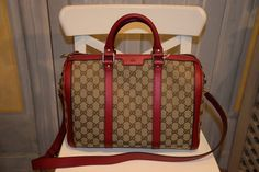 Bolso Gucci con piezas metálicas doradas y detalles rojos