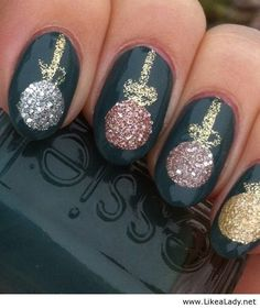 Christmas nail art with glittering festive baubles over a bang on trend green varnish background.