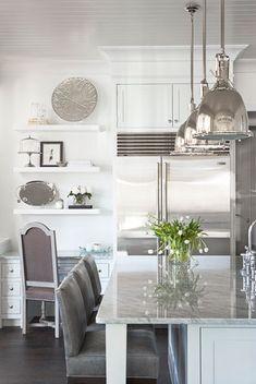 Carrara marble countertop, industrial pendants, Sub-Zero refrigerator, Michael Aram accessories, Perrin  Rowe faucet, leather barstools.  Design by Linda McDougald Design | Postcard from Paris Home.