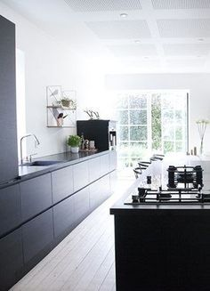 Black kitchen with exposed brick wall - via Coco Lapine Design