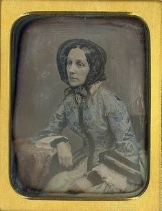 This woman seems so resigned, but to what? The tinting of the daguerteotype is subtle and well done. Her wristlets match the trim on the bell sleeves of her bodice, and her engageante are very fine.