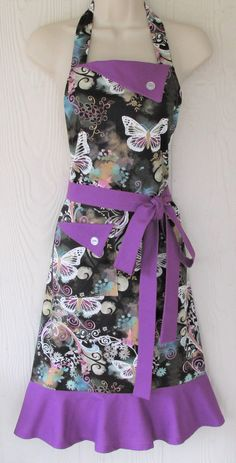 Butterfly Apron, Butterflies, Floral Apron, Womens Full Apron, Retro Style, KitschNStyle  This womens full apron in authentic retro style is a white, lacy butterfly and floral print against muted colors on a gray background.  The flaps, flounce and ties are a solid, vibrant shade of orchid. Ties are extra long to fit and flatter many body types and sizes. A sturdy, lined pocket in the front makes this apron perfectly practical for daily use.  Length: 33 Neck ties: 25 each Waist ties: 42…