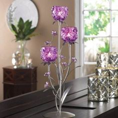 "This lovely candle holder features a silvery framework of leaves and stems that burst with bright fuchsia blooms. Three flower-pattern candle cups await the candles of your choice, surrounded by precious little glass flowers. Simply gorgeous!  Item weight: 2.4 lbs. 6½"" x 6″ x 17¾"" high. Iron, glass and acrylic. Candles not included."