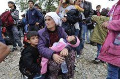 El número de llegadas de refugiados e inmigrantes a Grecia alcanza el medio millón © ACNUR/M.Henley.Una madre y sus hijos esperan junto a otros refugiados para entrar en el centro de recepción de Vinojug en Gevgelija.