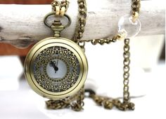 Detailed Antique Brass Quartz pocket watch with Swarovski twist coin and space connector chain accents. Finished with 18k Matte Gold and Antique Copper