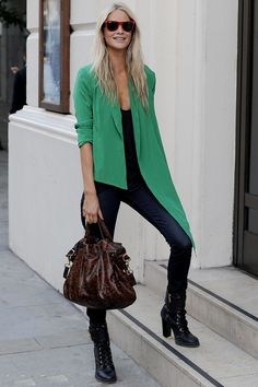 Poppy Delevingne in skinny jeans, which she teams with a green asymmetric jacket, red Ray Ban Wayfarers, black chunky heeled-boots and the Mulberry Alexa.