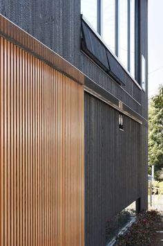 炭がしっかり残る焼き杉の外壁に、施主こだわりの格子戸が映える。 「周囲に緑が多いところでは黒い家が似合う。」と岸本さん。japan-architects.com