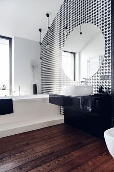 On ose le bois au plancher de la salle de bain pour donner de la chaleur à la salle de bain classique noire et blanche.