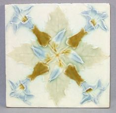 "A nice 6"" press molded tile of thistle flowers and leaves on an ivory background. It has soft pastel blue, green and tan glazes The thistle is the national flower and emblem of Scotland. The back is u"