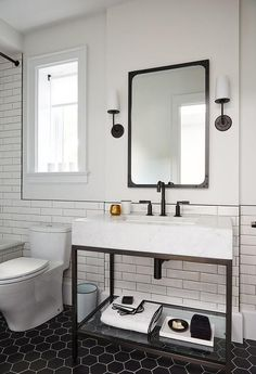 Modern black and white bathroom is lit by Modern Taper Sconces with Linen Shades mounted on either side of an Industrial Rivet Flat Mirror located above a Hudson Metal Single Washstand finished with a matte black faucet.