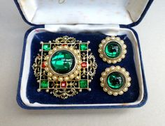 LARGE BROOCH AND MATCHING EARRINGS. GREEN GLASS AND PEARL CLIP EARRINGS. ALL HAVE THE ELIZABETH REIMER TRADE MARK ON THE BACK. EARRINGS ARE STAMPED ARCANSAS. LARGE GOLD TONE BROOCH. ORIGINAL BOX HAS SOME MARKS AND IS A BIT SHABBY.   eBay!
